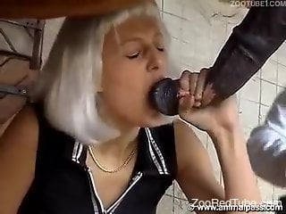 Mature woman is sucking a super massive stallion's dick