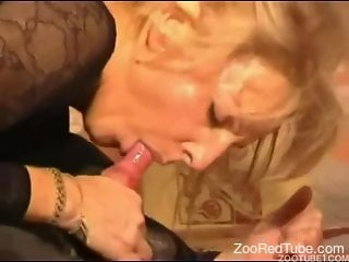 Blonde deepthroats a dog's cock on the couch
